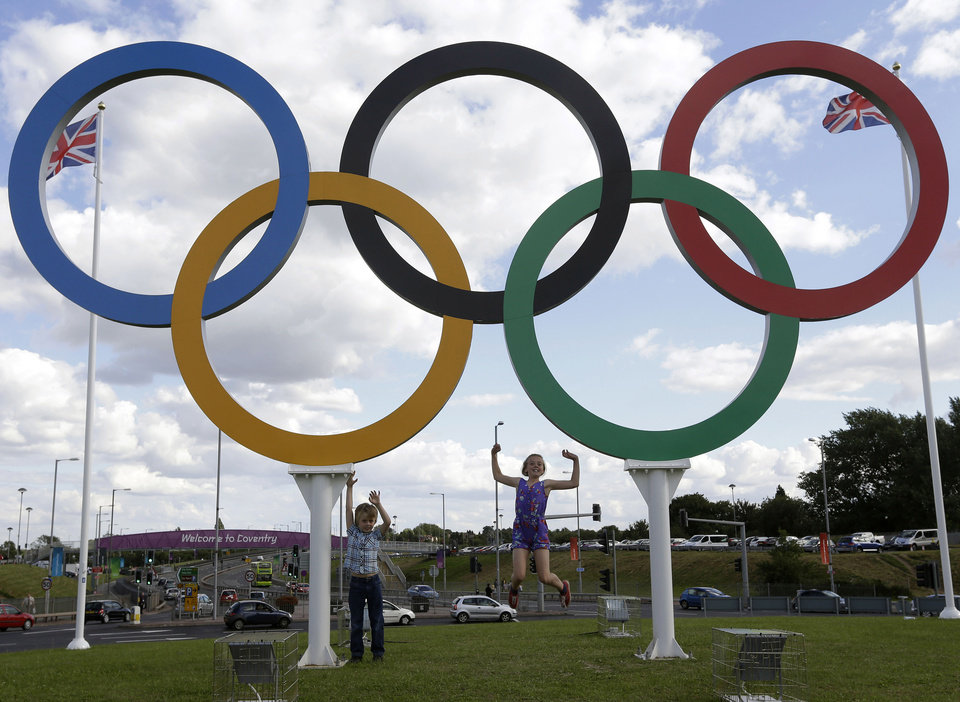 Photo - FILE - In this July 28, 2012 file photo, British children pose for photos under a sculpture of the Olympics rings, in Coventry, England. Boston, Los Angeles, San Francisco and Washington are the cities still in the running for a possible U.S. bid to host the 2024 Summer Olympics. (AP Photo/Hussein Malla, File)