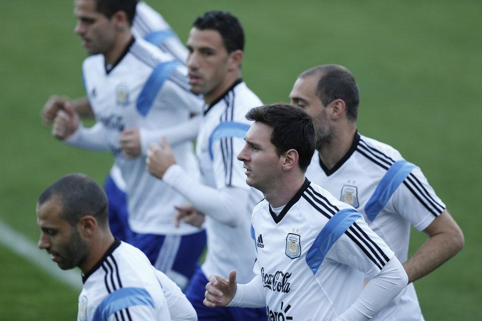 Photo - Argentina's Lionel Messi, center, jogs with teammates during a training session in Vespasiano, near Belo Horizonte, Brazil, Monday, June 16, 2014. Argentina plays in group F of the 2014 soccer World Cup. (AP Photo/Victor R. Caivano)