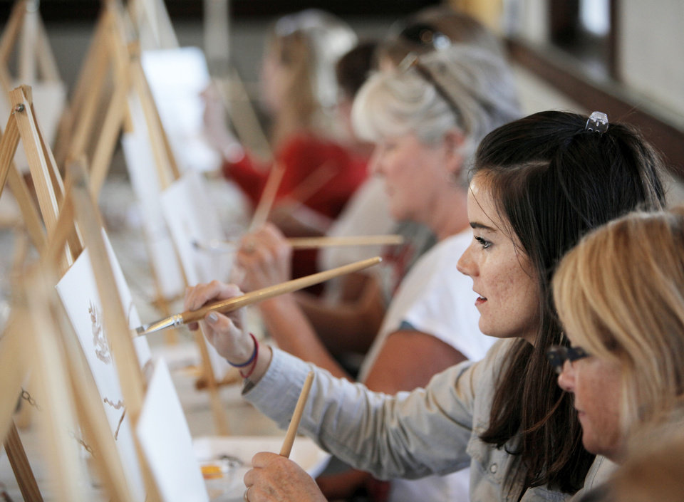 "Photo - Alyse Cox and other participants paint during the Performing Art Studio's ""Corkscrews and Canvas"" painting party Thursday at the Santa Fe Depot in Norman. PHOTOS BY NATE BILLINGS, THE OKLAHOMAN"
