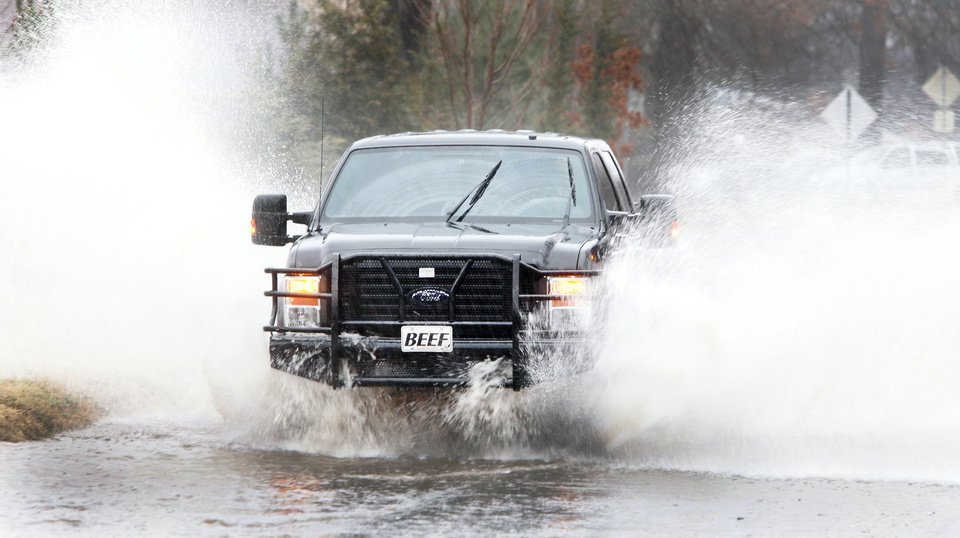 Photo - A pickup drives through high water Monday on W University Avenue in Stillwater.  Photo by Steve Gooch, The Oklahoman