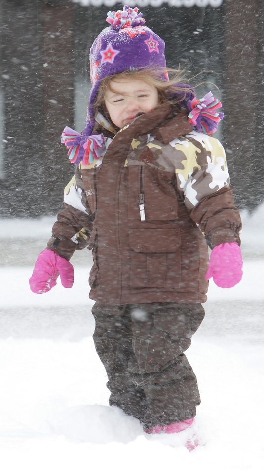 Photo - While Jeff Patton worked to clear the snow from in front of Classics Salon and Barber Shop in Edmond, daughter, Cheyenne, 2,  played in the snow in downtown Edmond, Wednesday, February 9 , 2011. Photo by David McDaniel, The Oklahoman