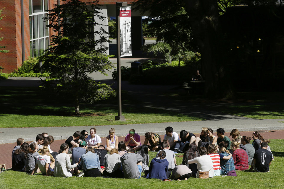 Photo - Students and other supporters form a prayer circle on the campus of Seattle Pacific University, Friday, June 6, 2014 in Seattle. Classes were canceled Friday following a shooting at Otto Miller Hall Thursday afternoon.  A 19-year-old man was fatally shot and two other young people were wounded after a gunman entered the foyer  and started shooting.  Aaron R. Ybarra, 26, was booked into the King County Jail late Thursday for investigation of homicide, according to police and the jail roster. (AP Photo/Ted S. Warren)