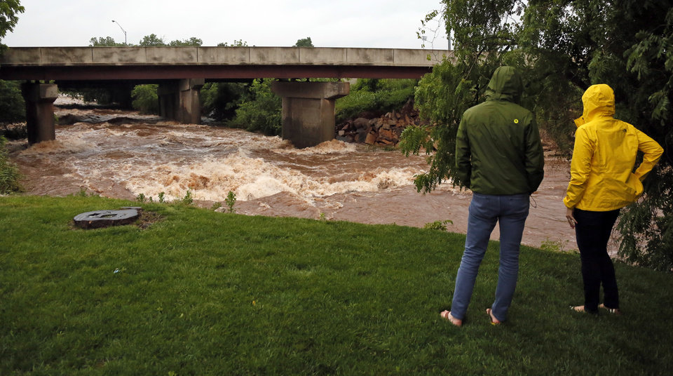 Photo - People watch as water rushes down the Deep Fork River underneath I-44 during a thunder storm in Oklahoma City, Saturday, May 23, 2015. Photo by Nate Billings, The Oklahoman