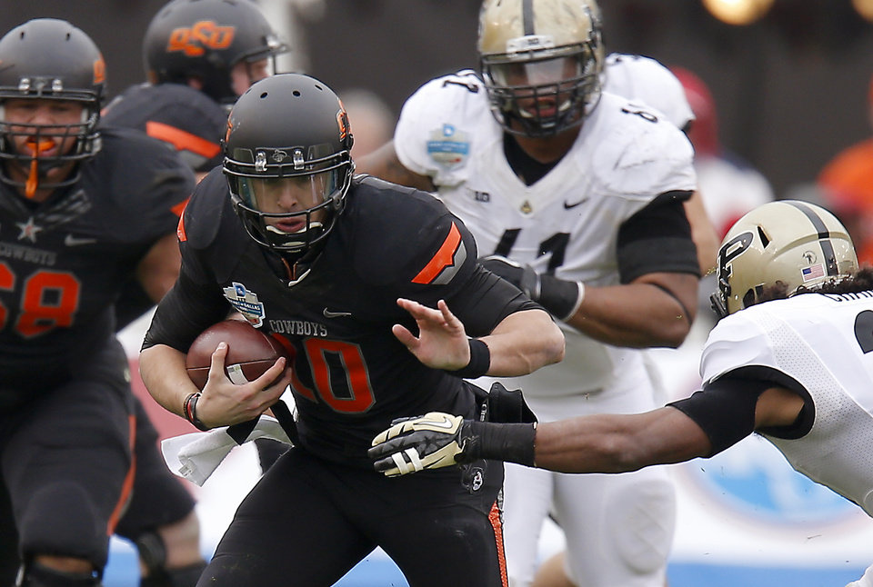 Oklahoma State\'s Clint Chelf (10) runs past Purdue\'s Max Charlot (34) during the Heart of Dallas Bowl football game between Oklahoma State University and Purdue University at the Cotton Bowl in Dallas, Tuesday, Jan. 1, 2013. Oklahoma State won 58-14. Photo by Bryan Terry, The Oklahoman