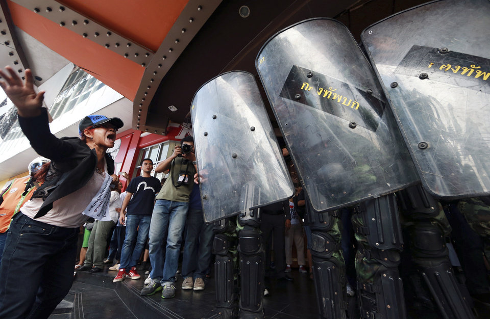 Photo - A woman protester yells at Thai soldiers as they move in to disperse the protesters against the coup outside a shopping complex in Bangkok, Thailand Saturday, May 24, 2014. Thailand's coup leaders said Saturday they will keep former Prime Minister Yingluck Shinawatra, Cabinet members and anti-government protest leaders detained for up to a week to give them