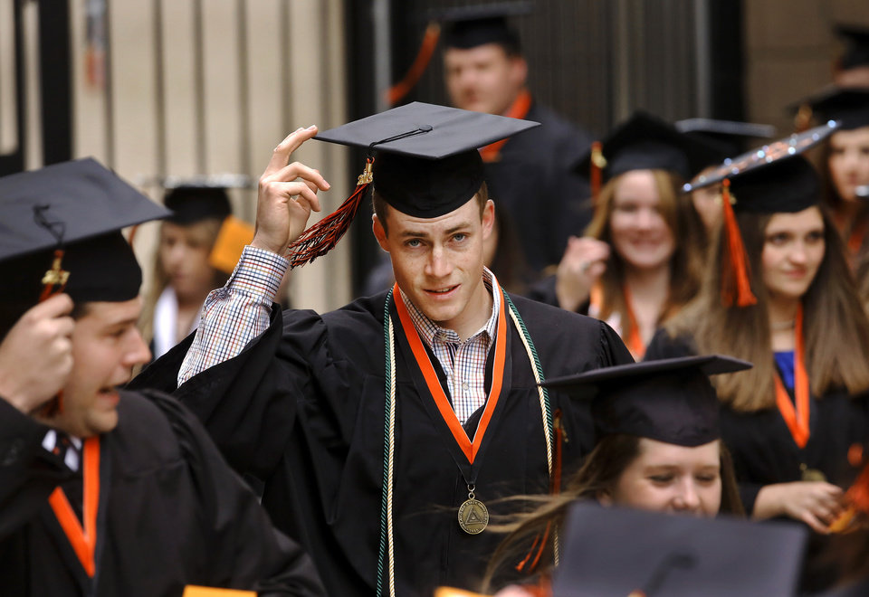Graduates adjust their caps to keep them on their heads in the wind as they walk to the arena. Undergraduates at OSU participated in the school's 127th commencement ceremony the weekend of Friday, May 3 and Saturday, May 4, 2013 inside Gallagher-Iba Arena on the university's campus.These photos were taken at the Saturday morning ceremony when students from the College of Agricultural Sciences and Natural Resources, and the Spears School of Business were conferred with degrees.   Photo  by Jim Beckel, The Oklahoman.