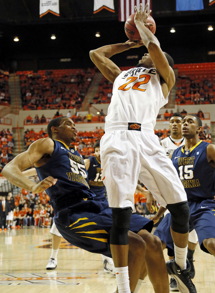 Photo - West Virginia's Keaton Miles (55) commits a blocking foul against Oklahoma State's Markel Brown (22) during an NCAA men's basketball game between Oklahoma State University (OSU) and West Virginia at Gallagher-Iba Arena in Stillwater, Okla., Saturday, Jan. 26, 2013. Photo by Nate Billings, The Oklahoman