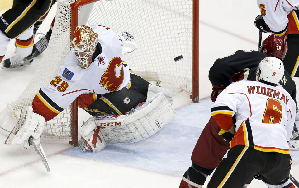 Photo - Calgary Flames' Reto Berra (29), of Switzerland, gives up a goal to Phoenix Coyotes' Shane Doan (19) as Flames' Dennis Wideman (6) defends during the second period of an NHL hockey game, Tuesday, Jan. 7, 2014, in Glendale, Ariz. (AP Photo/Ross D. Franklin)