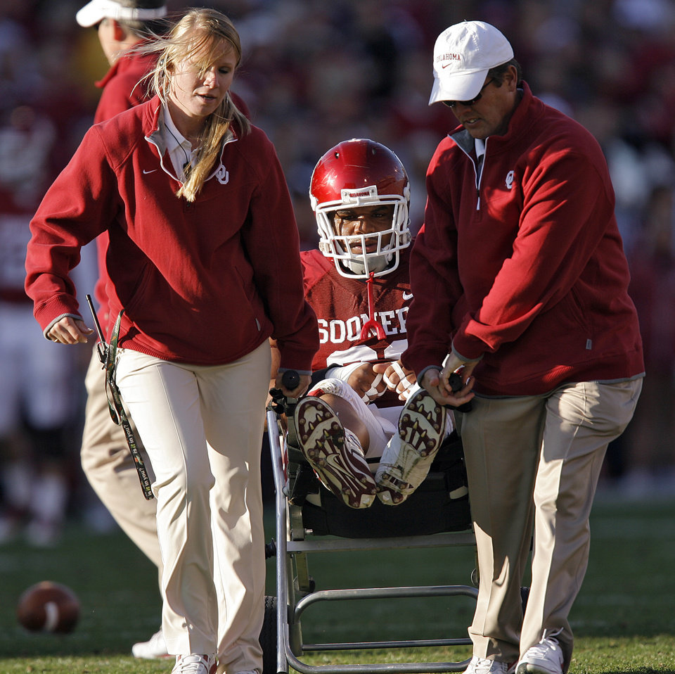 Photo - Oklahoma's Adrian Taylor (86) is carted off the field with a leg injury by the trainers during the first half of the college football game between the University of Oklahoma Sooners (OU) and the Texas Tech Red Raiders (TTU) at the Gaylord Family Memorial Stadium on Saturday, Nov. 13, 2010, in Norman, Okla.  Photo by Chris Landsberger, The Oklahoman