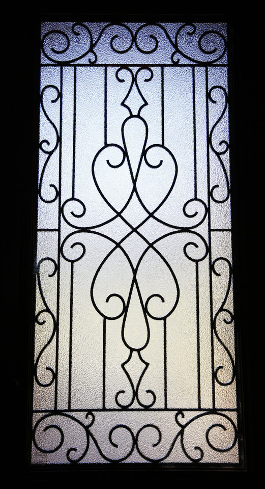 Daylight appears through a wrought iron-decorated door panel in a model home by SWM & Sons at 12005 Tuscany Ridge Road in Midwest City. Photo by Paul B. Southerland, The Oklahoman PAUL B. SOUTHERLAND