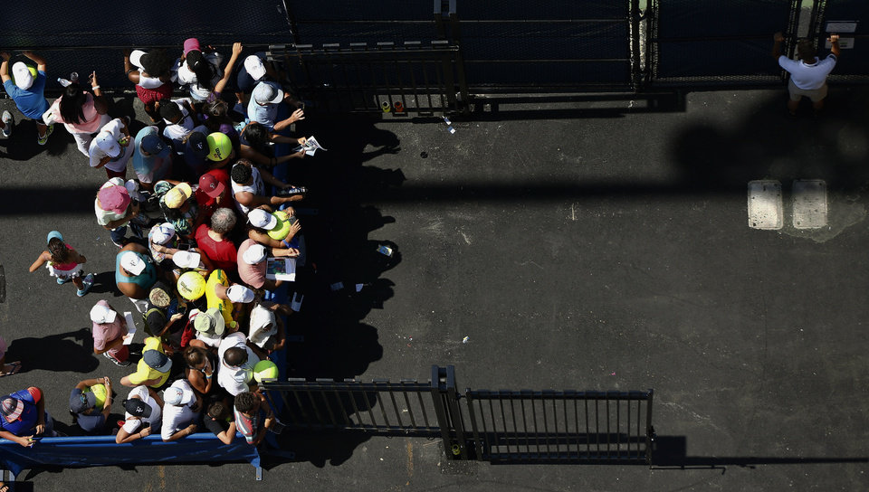 Photo - Tennis fans wait outside the practice courts for autographs from players during the second round of the 2014 U.S. Open tennis tournament, Wednesday, Aug. 27, 2014, in New York. (AP Photo/Matt Rourke)