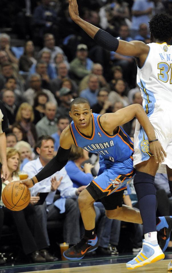 Photo - Oklahoma City Thunder guard Russell Westbrook (0) drives past Denver Nuggets center Nene (31) from Brazil during the first half of game 3 of a first-round NBA basketball playoff series Saturday, April 23, 2011, in Denver. (AP Photo/Jack Dempsey)