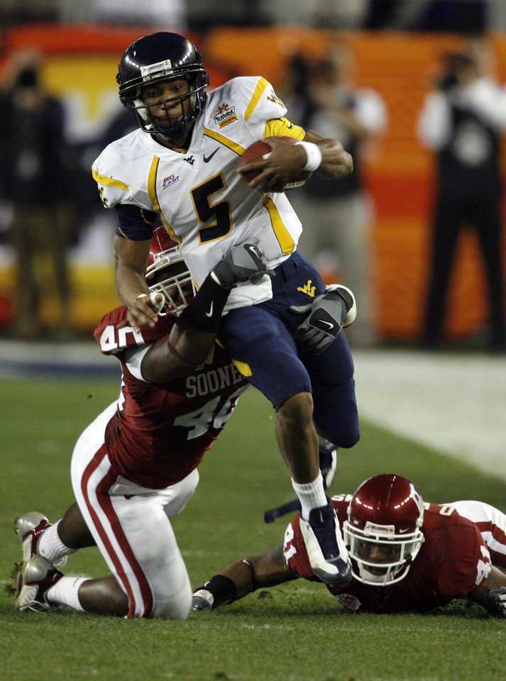 Photo - Patrick White eludes the tackle of Curtis Lofton during the first half of the Fiesta Bowl college football game between the University of Oklahoma Sooners (OU) and the West Virginia University Mountaineers (WVU) at The University of Phoenix Stadium on Wednesday, Jan. 2, 2008, in Glendale, Ariz. 