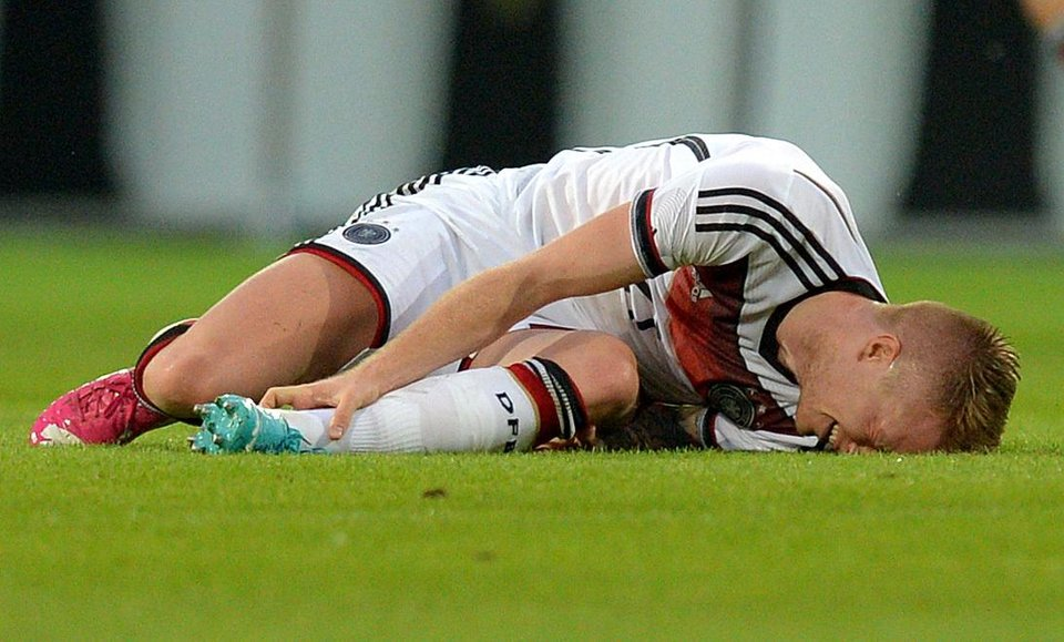 Photo - In this picture taken Friday June 6, 2014 German national soccer player  Marco Reus  lies on the pitch during the friendly soccer match between Germany and Armenia in Mainz Germany. Reus was helped off the pitch  after twisting his left ankle while challenging Artur Yedigaryan for the ball. Reus immediately dropped to the grass and appeared in considerable pain. Team doctor Hans-Wilhelm Mueller-Wohlfahrt shook his head as he assisted the Borussia Dortmund player off the pitch. Reus was taken to the hospital to determine the full extent of the injury. AP Photo/dpa,Thomas Eisenhuth)
