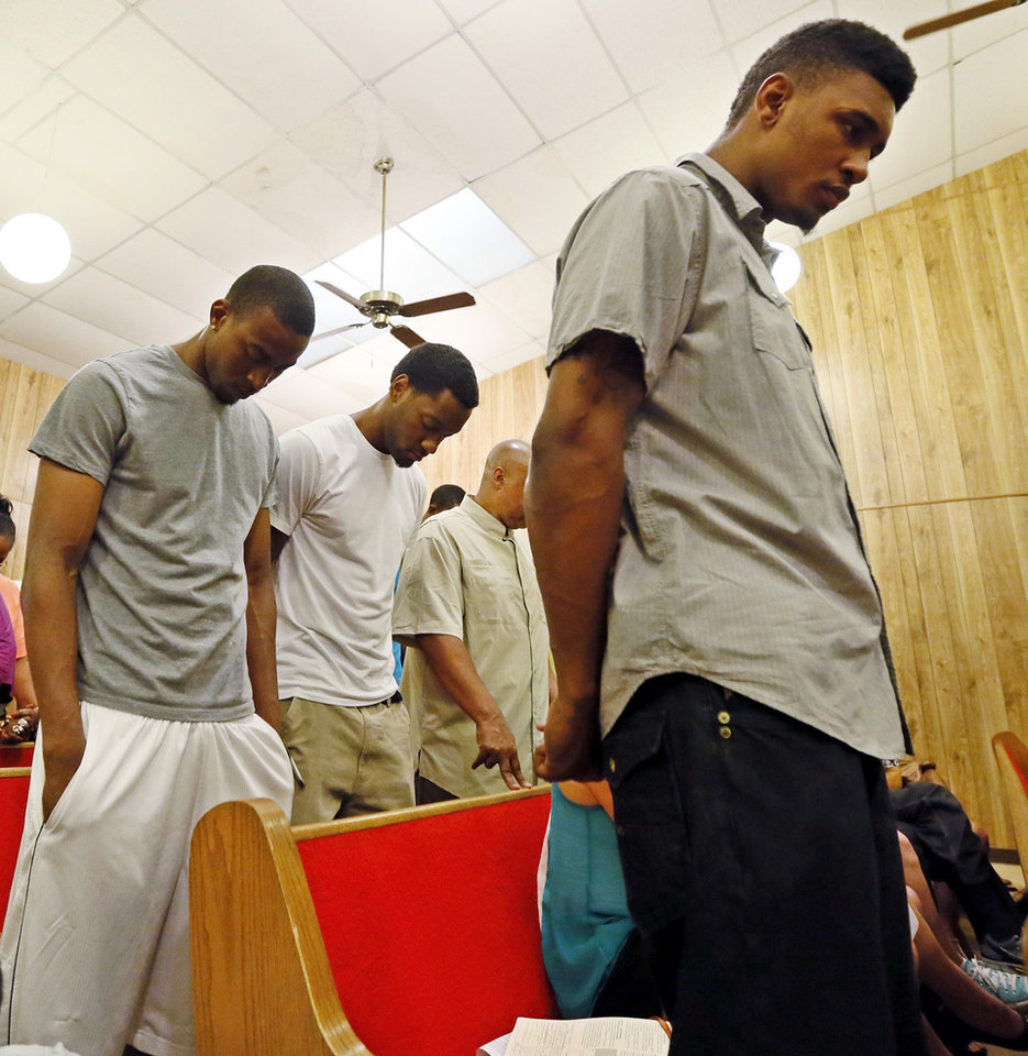 Photo - OSU basketball players Le'Bryan Nash, right, Markel Brown, left, and Brian Williams, middle, bow their heads during a prayer at a rally in support of their teammate Darrell Williams at Mt. Zion Baptist Church in Stillwater, Okla., Thursday, Aug. 23, 2012. Williams, a suspended Oklahoma State basketball player, was found guilty on two counts of rape by instrumentation and one count of sexual battery after an incident at a house party. Photo by Nate Billings, The Oklahoman