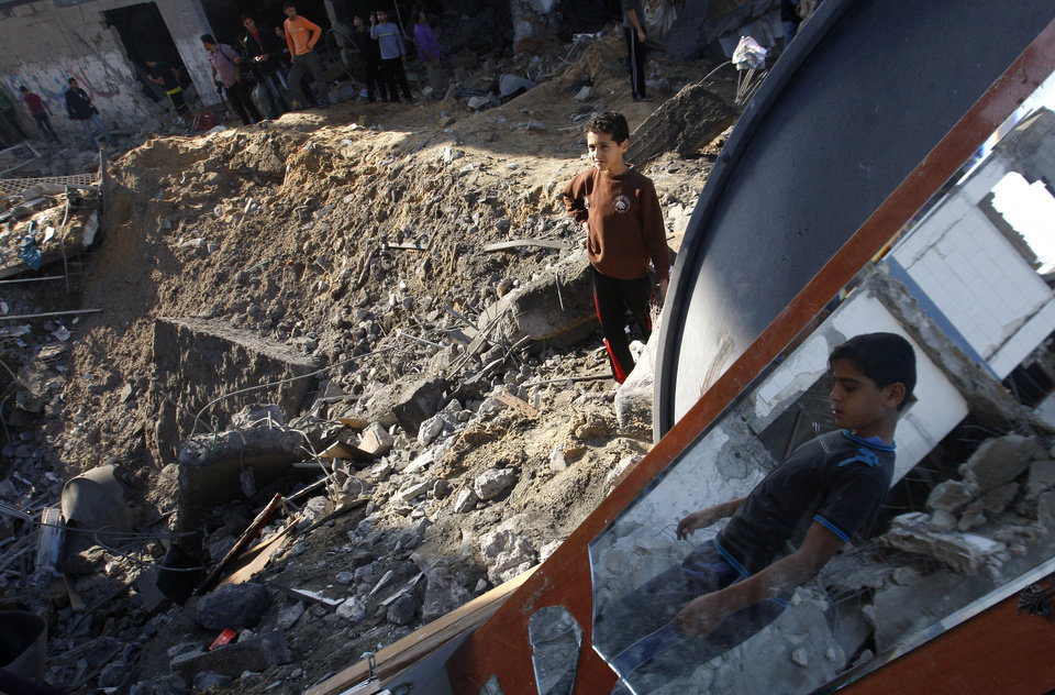 Photo -   Palestinian children stand in the rubble left after an Israeli strike on a house in Gaza City, Tuesday, Nov. 20, 2012. Efforts to end a week-old convulsion of Israeli-Palestinian violence drew in the world's top diplomats on Tuesday, with President Barack Obama dispatching his secretary of state to the region on an emergency mission and the U.N. chief appealing from Cairo for an immediate cease-fire. (AP Photo/Hatem Moussa)
