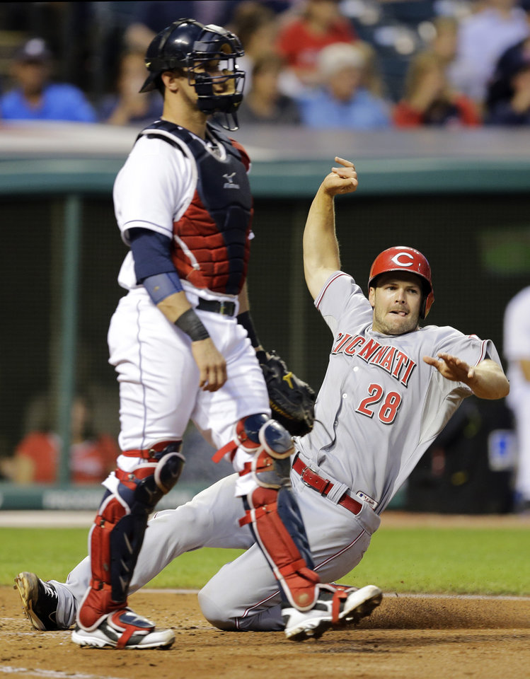 Photo - Cincinnati Reds' Chris Heisey (28) slides past Cleveland Indians catcher Yan Gomes to score on a steal from third as Brayan Pena is caught stealing second in the fifth inning of a baseball game Tuesday, Aug. 5, 2014, in Cleveland. (AP Photo/Mark Duncan)