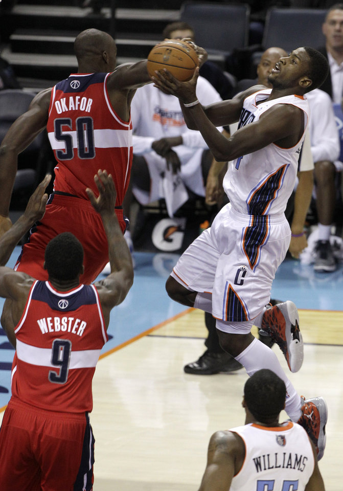 Charlotte Bobcats' Michael Kidd-Gilchrist, right, drives to the basket against Washington Wizards' Emeka Okafor, left, and Martell Webster, bottom, during the first half of an NBA basketball game in Charlotte, N.C., Tuesday, Nov. 13, 2012. (AP Photo/Chuck Burton)