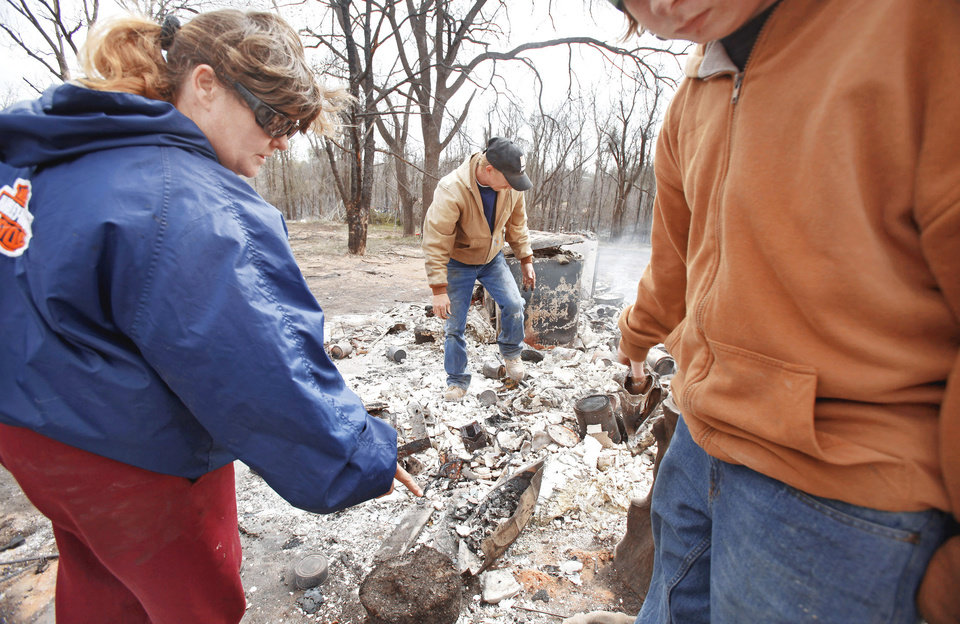 Photo - Carrie Wertz and her husband, Kenneth,  try Friday to salvage items from their  destroyed home in Choctaw.  Photo by Chris Landsberger, The Oklahoman