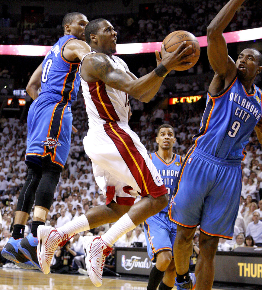 Photo - Miami's Mario Chalmers (15) goes to the basket between Oklahoma City's Russell Westbrook (0) and Oklahoma City's Serge Ibaka (9) during Game 4 of the NBA Finals between the Oklahoma City Thunder and the Miami Heat at American Airlines Arena, Tuesday, June 19, 2012. Oklahoma City lost 104-98.  Photo by Bryan Terry, The Oklahoman