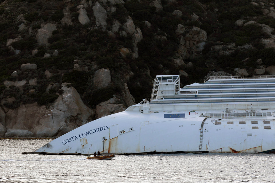 Photo -   A view of the partially sunk Costa Concordia wreckage next to the Giglio Island, Italy, Sunday, Oct. 14, 2012. The first hearing of the trial for the Jan. 13, 2012 tragedy, where 32 people died after the luxury cruise Costa Concordia was forced to evacuate some 4,200 passengers after it hit a rock while passing too close to the Giglio Island, is taking place in Grosseto Monday Oct. 15, 2012. Captain Schettino, who was blamed for both the accident and for leaving the ship before the passengers, is scheduled to attend the hearing. (AP Photo/Gregorio Borgia)