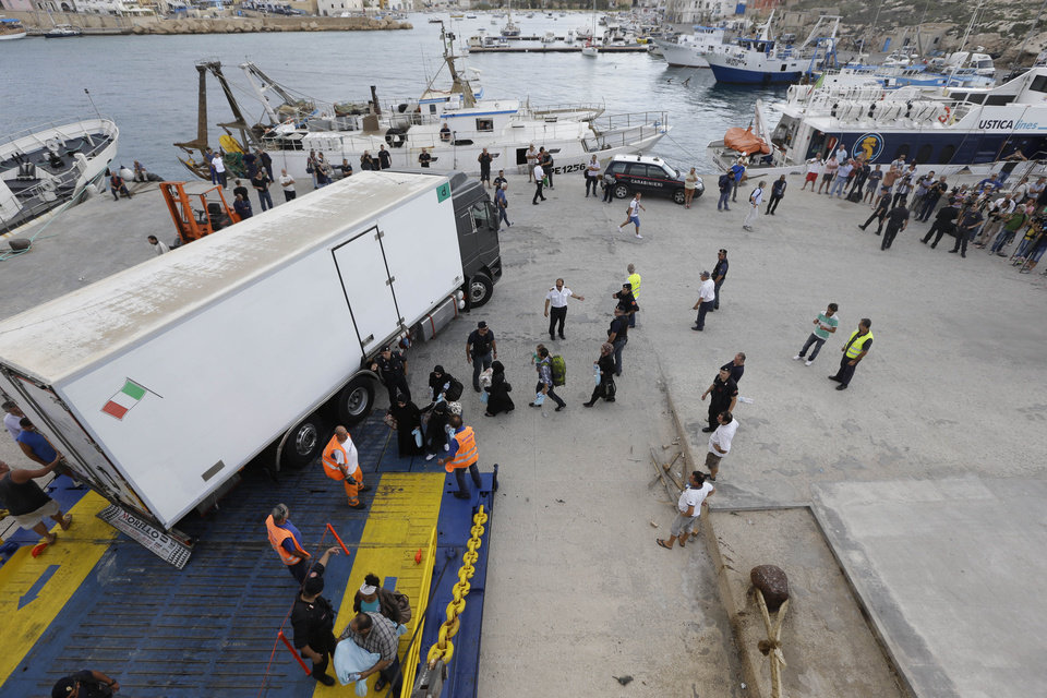 Photo - Migrants board a ship heading to Sicily, in Lampedusa, Italy, Friday, Oct. 4, 2013. A boat carrying African migrants toward Italy caught fire and capsized off the Sicilian island of Lampedusa Thursday, spilling hundreds of passengers into the sea. Over one hundred bodies were recovered but over 200 people are unaccounted-for. It was one of the deadliest accidents in recent times during the notoriously perilous crossing from Africa for migrants seeking a new life in the European Union. (AP Photo/Luca Bruno)