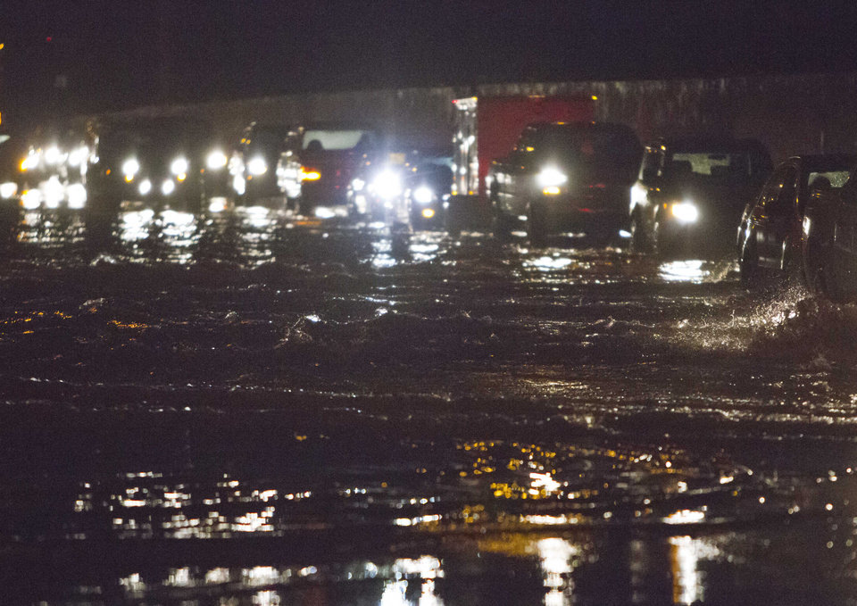 Photo - Westbound traffic on I-44 at Linclon Blvd. drives through flood water on I-44 after a thunderstorm goes through Oklahoma City on Friday, May 31, 2013. (AP Photo/Alonzo Adams)