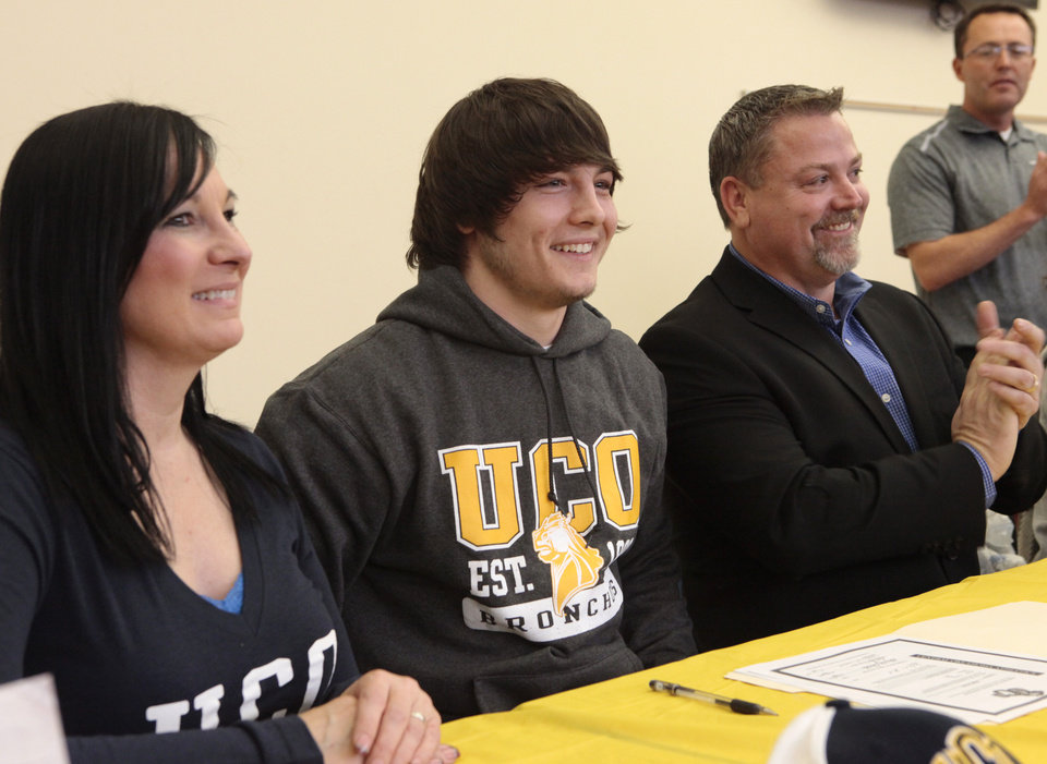 Photo - Eli Hooks, center, with his parents, Teri Garris and Bryan Hooks, during signing day at Deer Creek High School, Wednesday, February 4, 2014. Eli signed with UCO. Photo by David McDaniel, The Oklahoman