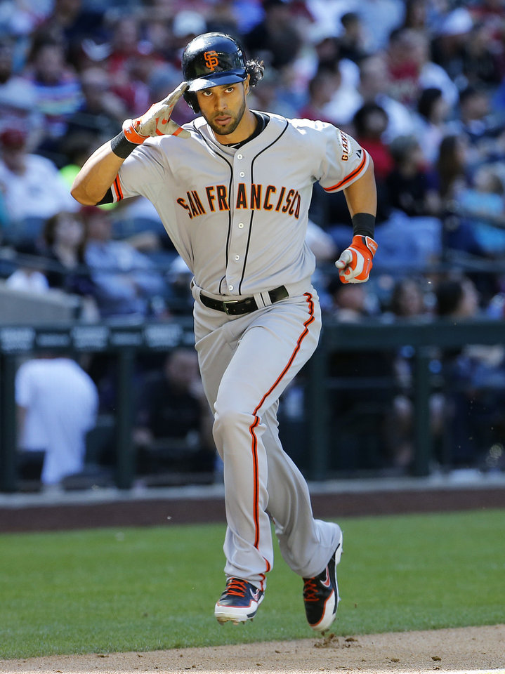 Photo - San Francisco Giants center fielder Angel Pagan salutes the Giants dugout as he rounds the bases after hitting a three-run home run against the Arizona Diamondbacks during the eighth inning of a baseball game Thursday, April 3, 2014, in Phoenix. (AP Photo/Matt York)