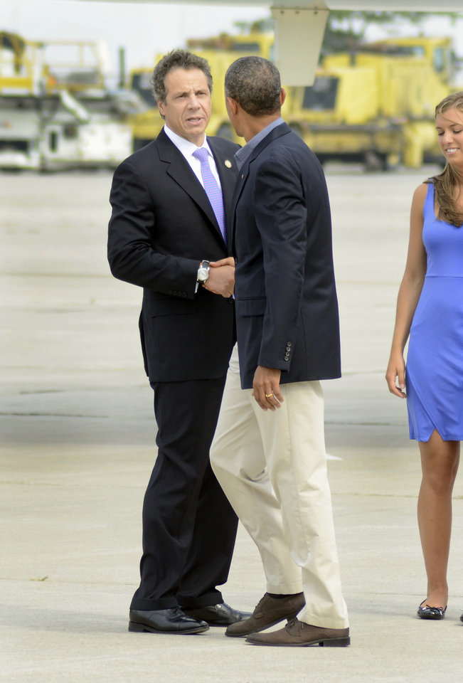 Photo - New York State Gov. Andrew Cuomo shakes hands with President Barack Obama after Obama arrived at Buffalo Niagara International Airport in Buffalo, N.Y.,, Thursday, August 22, 2013. (AP photos/Heather Ainsworth)