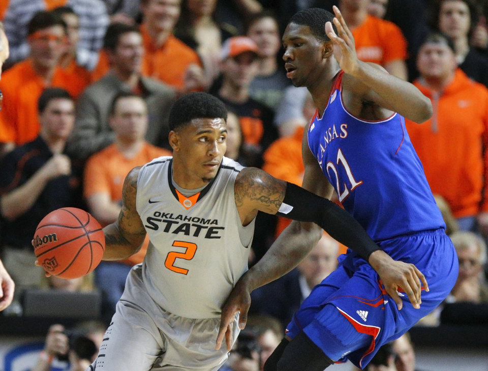 Photo - Oklahoma State's Le'Bryan Nash (2) goes around Kansas' Joel Embiid (21) during an NCAA college basketball game between Oklahoma State University (OSU) and the University of Kansas at Gallagher-Iba Arena in Stillwater, Okla., Saturday, March 1, 2014. Photo by Bryan Terry, The Oklahoman