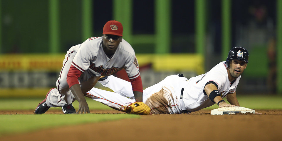 Photo - Miami Marlins' Garrett Jones, right, and Arizona Diamondbacks shortstop Didi Gregorius watch the latter's throw to first that completed a double play of Jarrod Saltalamacchia during the first inning of a baseball game in Miami, Friday, Aug. 15, 2014. (AP Photo/J Pat Carter)