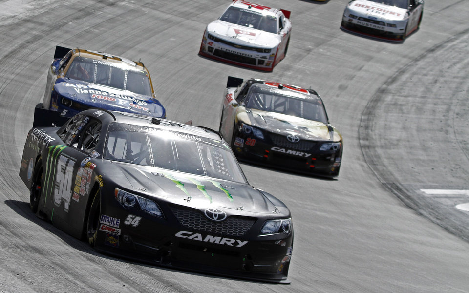 Photo - Driver Kyle Busch (54) races with Matt Kenseth (20) and Kevin Harvick (5) during the NASCAR Nationwide series auto race at Bristol Motor Speedway on Saturday, March 15, 2014, in Bristol, Tenn. Busch won the race. (AP Photo/Wade Payne)