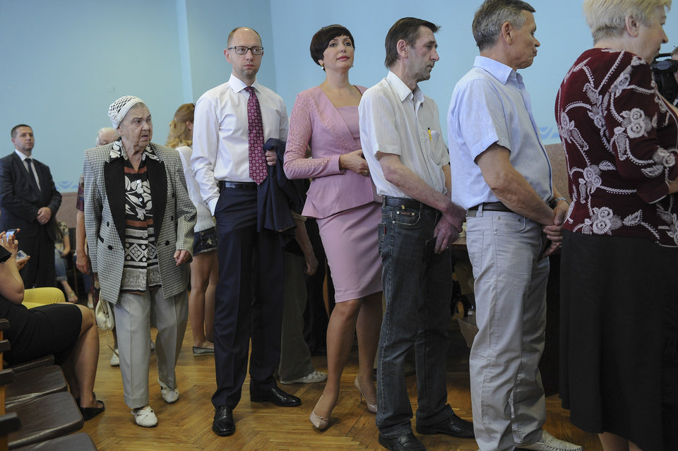 Photo - Ukrainian Prime Minister Arseniy Yatsenyuk, second left,  stands in line to receive his ballot at a polling station during presidential and mayoral elections in Kiev, Ukraine, Sunday, May, 25, 2014. Ukraine's critical presidential election got underway Sunday under the wary scrutiny of a world eager for stability in a country rocked by a deadly uprising in the east. (AP Photo/Andrew Kravchenko, pool)