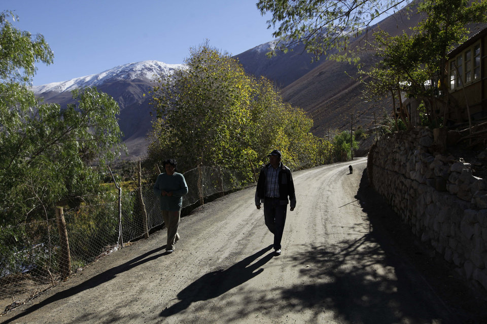 Photo - In this May 23, 2013 photo, two men walk along a road in El Corral, a small town of about 200 inhabitants, mostly from the Diaguita ethnic group, near the facilities of Barrick Gold Corp's Pascua-Lama project in northern Chile. The Diaguitas live in the foothills of the Andes, where for as long as anyone can remember they've drunk straight from the glacier-fed river that irrigates their orchards and vineyards with clean water. But since Pascua-Lama gold mine project moved in, the Diaguitas claim the river levels have dropped and some complain of cancerous growths and aching stomachs. (AP Photo/Jorge Saenz)