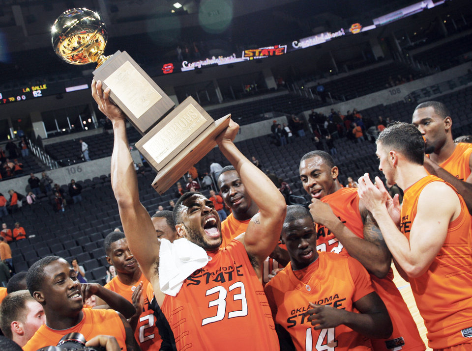 OSU's Marshall Moses raises the All-College Classic trophy after the Cowboys beat La Salle 77-62 Monday night at the Ford Center.  PHOTO BY NATE BILLINGS, THE OKLAHOMAN