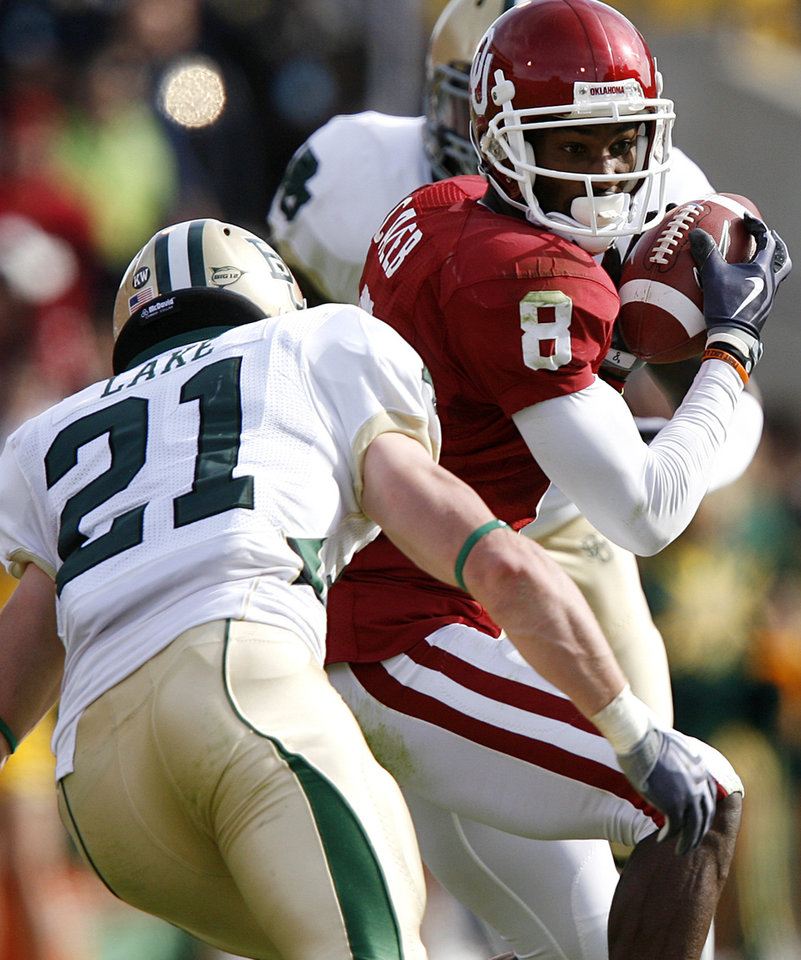 Photo - Oklahoma's Brandon Caleb (8) looks to get past Baylor's Jordan Lake (21) during the first half of the college football game between the University of Oklahoma Sooners (OU) and the Baylor University Bears at Gaylord Family-Oklahoma Memorial Stadium on Saturday, Oct. 10, 2009, in Norman, Okla. 