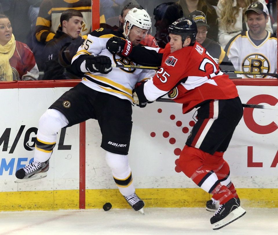 Ottawa Senator's Chris Neil (25) and Boston Bruins' Aaron Johnson (45) battle along the board for the puck during the first period of an NHL hockey game in Ottawa Thursday March 21, 2013.(AP Photo/The Canadian Press, Fred Chartrand)