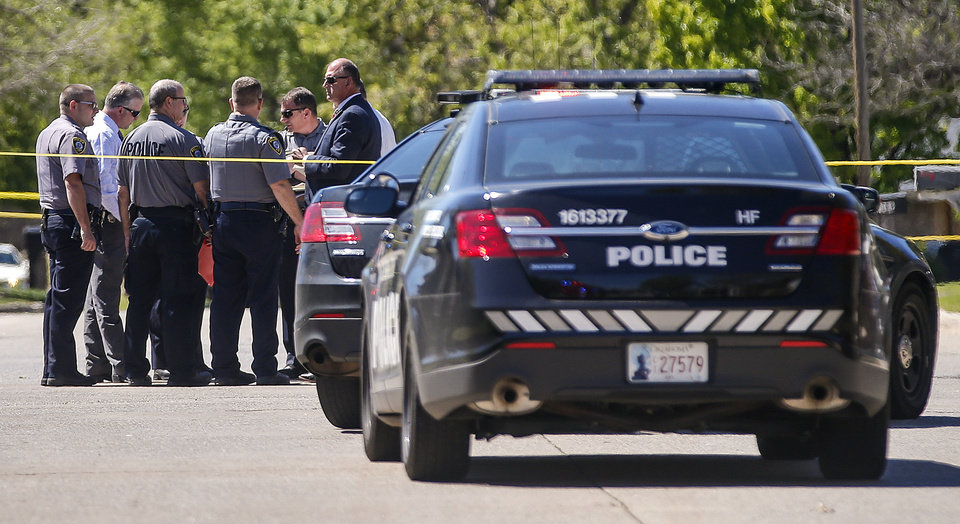 Photo -  Oklahoma City police gather at the scene where a woman and her dog were mauled to death by two large dogs on Thursday. [Photo by Chris Landsberger, The Oklahoman]