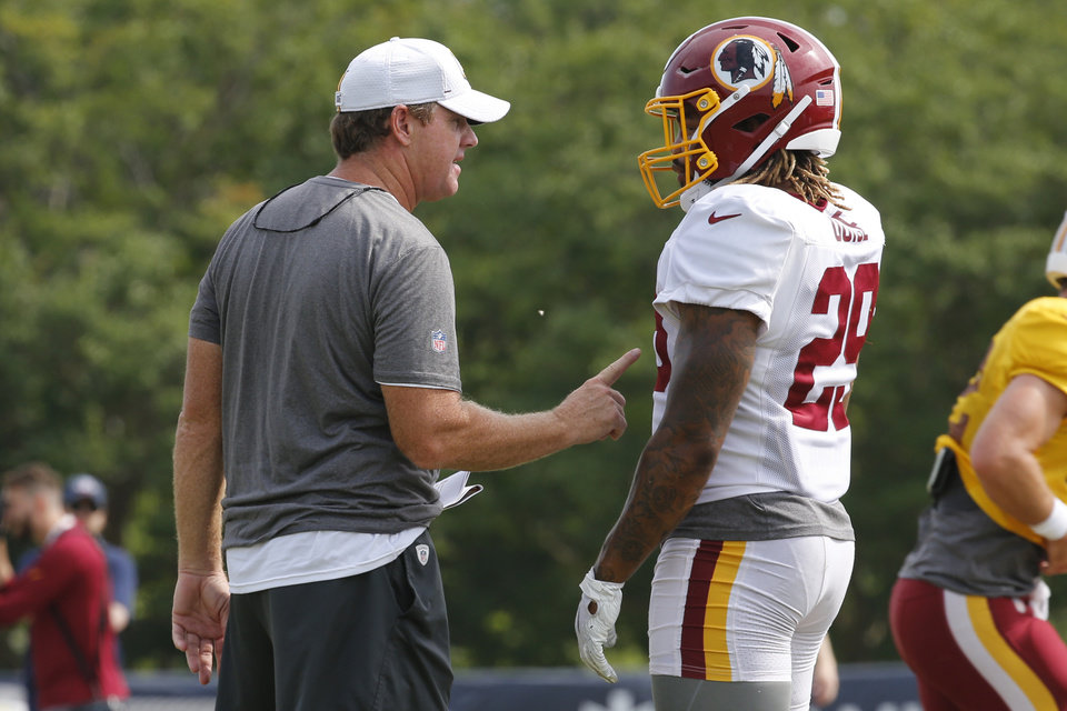 Photo - Washington Redskins head coach Jay Gruden, left, talks with running back Derrius Guice (29) during NFL football training camp in Richmond, Va., Monday, Aug. 5, 2019. (AP Photo/Steve Helber)