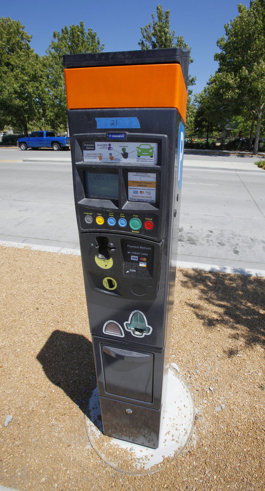 Photo - New electronic parking meters went live Monday in Oklahoma City. The meter prints receipts to be placed in parked cars.  PAUL B. SOUTHERLAND - The Oklahoman