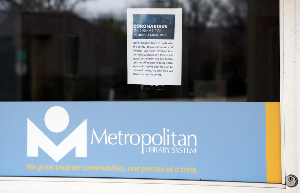 Photo - A sign on an entrance to the Belle Isle Library, 5501 N Villa Ave., says the library is closed because of the coronavirus pandemic, in Oklahoma City, Monday, March 16, 2020. The Metropolitan Library System is closed for at least two weeks. [Nate Billings/The Oklahoman]