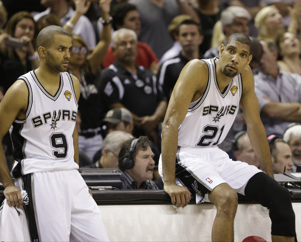 Photo - San Antonio Spurs' Tony Parker (9) and Tim Duncan (21) wait on the sideline against the Miami Heat during the first half at Game 4 of the NBA Finals basketball series, Thursday, June 13, 2013, in San Antonio. (AP Photo/Eric Gay)