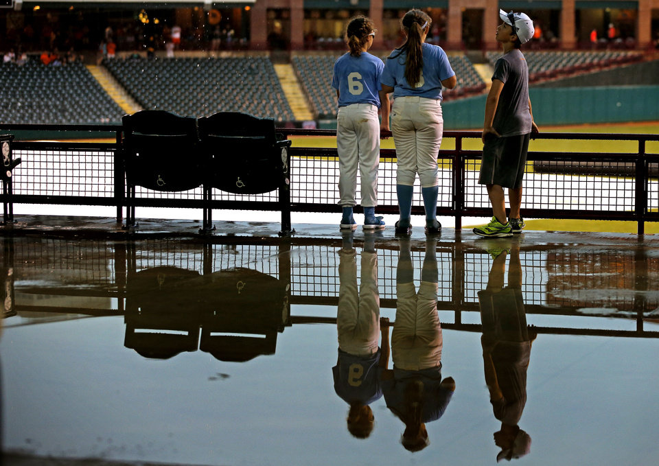 Photo - Parker Hayes, left, Haiden Parker, 9, and Cole Hayes, 11, are reflected in water as they pass time during a rain delay in a Big 12 Tournament baseball game between Oklahoma State University and the University of Texas at Chickasaw Bricktown Ballpark in Oklahoma City, Saturday, May 24, 2014. Photo by Bryan Terry The Oklahoman