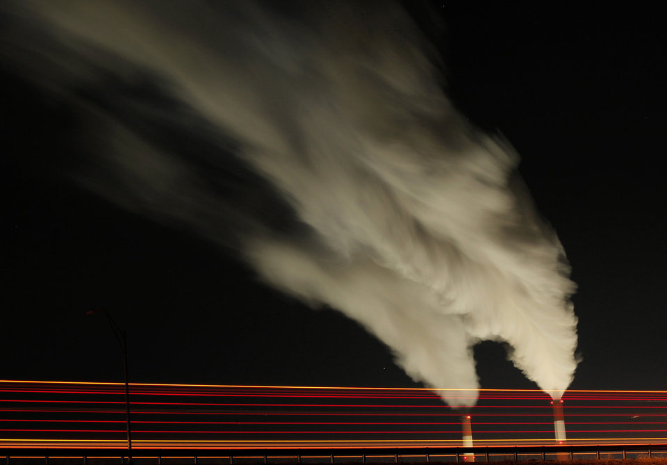 Photo - FILE - In this Jan. 19, 2012 file photo, smoke rises in this time exposure image from the stacks of the La Cygne Generating Station coal-fired power plant in La Cygne, Kan. The United Nations climate chief is urging people not to look solely to their governments to make tough decisions to slow global warming, and instead to consider their own role in solving the problem. Approaching the half-way point of two-week climate talks in Doha, Christiana Figueres, the head of the U.N.'s climate change secretariat, said Friday, Nov. 30, 2012 that she didn't see