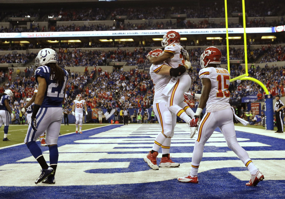 Photo - After scoring a 10-yard touchdown reception, Kansas City Chiefs running back Knile Davis (34) jumps into the arms of Geoff Schwartz (74) as wide receiver A.J. Jenkins (15) moves in during the second half of an NFL wild-card playoff football game Saturday, Jan. 4, 2014, in Indianapolis. Colts defensive back Josh Gordy (27) walks away. (AP Photo/AJ Mast)