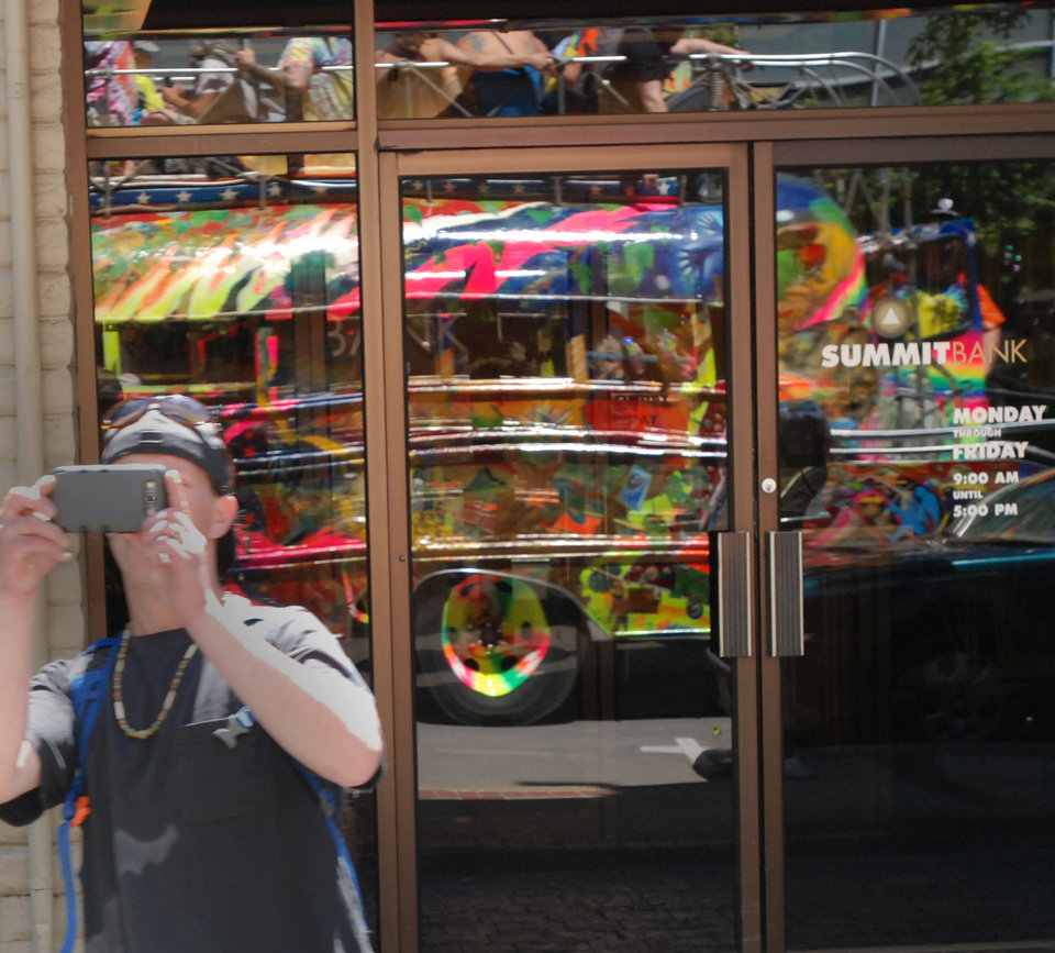 Photo - A man snaps a photo of the latest version of late author Ken Kesey's psychedelic bus Further, reflected in a window, as it drives through Eugene, Ore. Zane Kesey, the author's son, is on Kickstarter raising money for a trip across America commemorating the 50th anniversary of his father's 1964 trip, which became an icon of the 1960s. (AP Photo/Jeff Barnard)