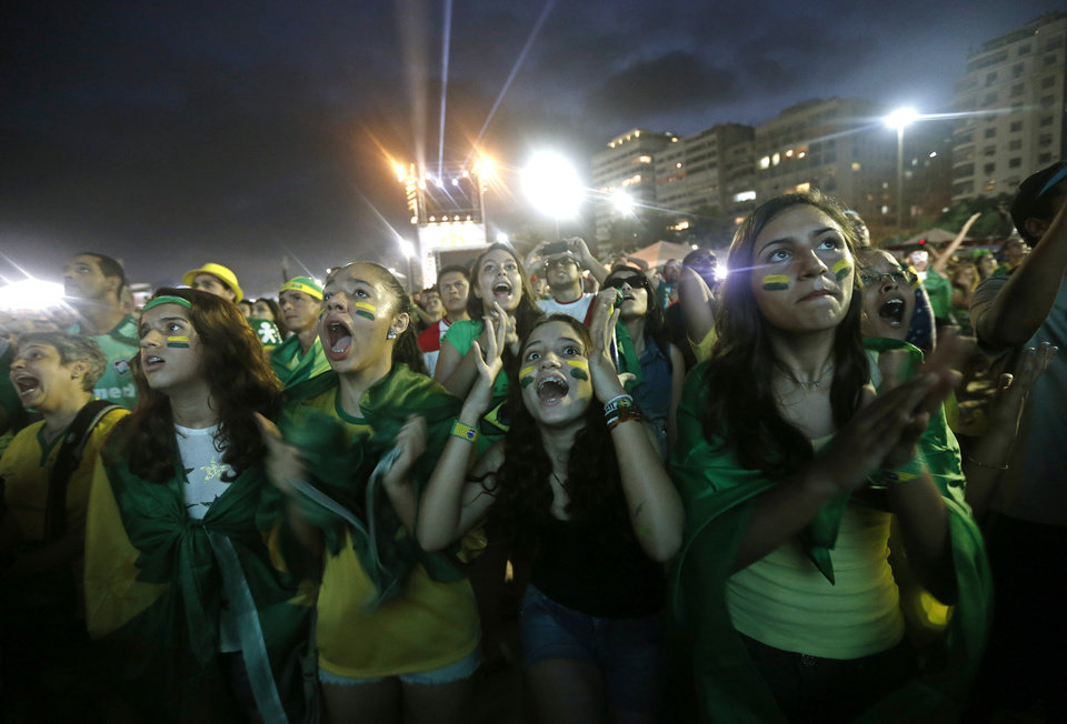 Photo - Soccer fans of the Brazil national soccer team react during a live broadcast of the soccer World Cup match between Brazil and Mexico, inside the FIFA Fan Fest area on Copacabana beach, in Rio de Janeiro, Brazil, Tuesday, June 17, 2014. Mexico claimed a deserved point against Brazil in a largely frustrating Group A game which finished 0-0 at Estadio Castelao in Fortaleza. (AP Photo/Silvia Izquierdo)