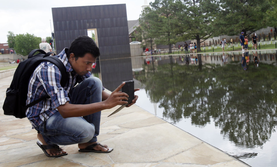 "Photo -  A student stops to photograph the bombing memorial's reflection pool. Students from India, Sri Lanka, Bangladesh and Nepal visited the OKC Bombing Museum and Memorial  on Friday, May 31, 2013. The group is here on a grant with the Gaylord College of Journalism at OU to study ""new journalism"", which includes the use of Twitter, smart phones, etc. Photo by Aliki Dyer The Oklahoman"