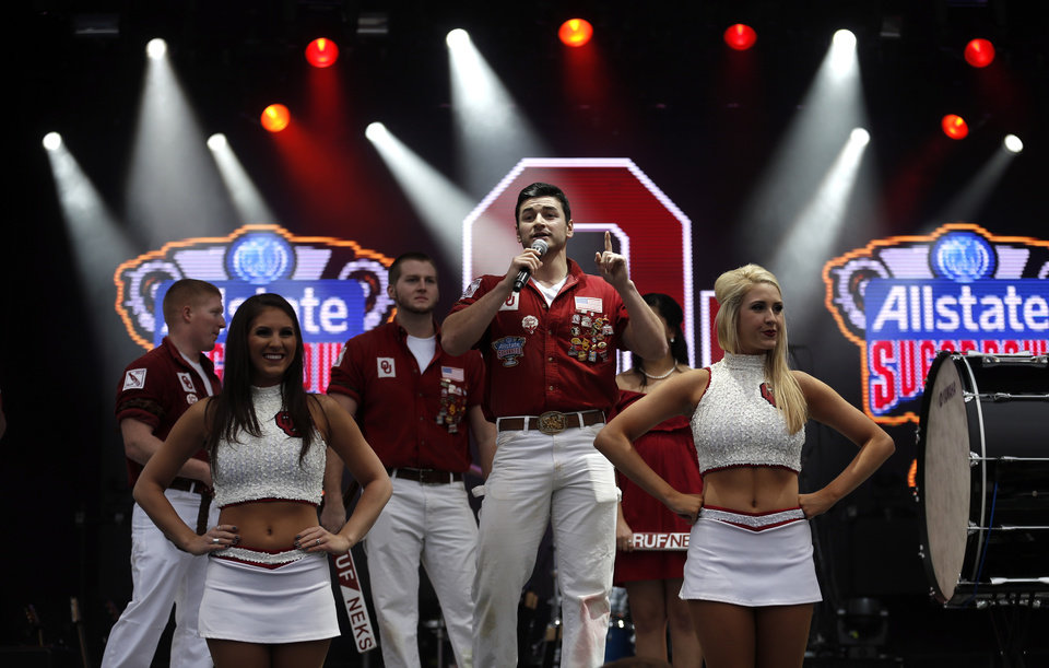 Photo - Ruffneck Bobby Nash and cheerleaders entertain the crowd during an Oklahoma pep rally in the French Quarter, Wednesday, Jan. 1, 2014 in New Orleans. Photo by Sarah Phipps, The Oklahoman